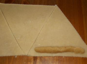 ضعي عجينة اللوز على طرف المثلث